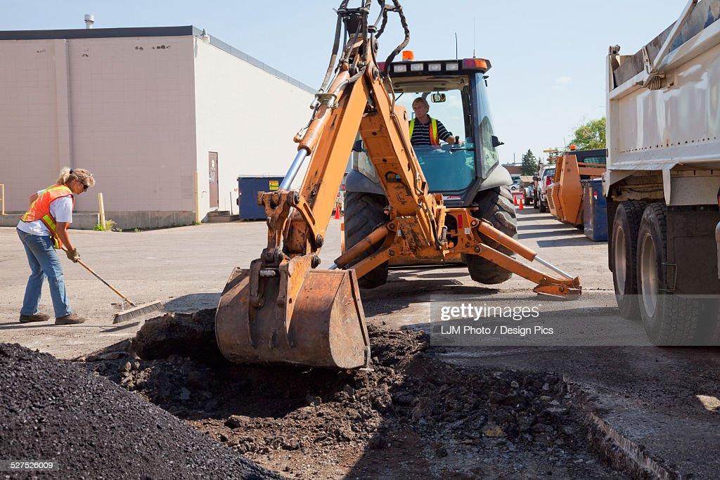 Work crew repairing pot holes in a parking lot
