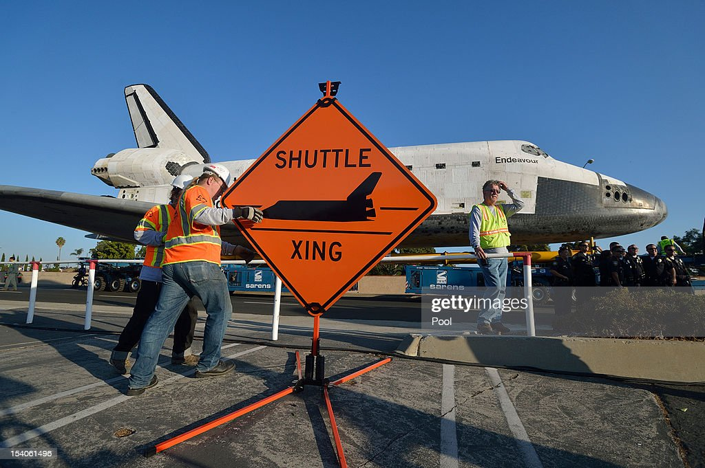 Work crews set up a sign as the Space Shuttle Endeavour arrives at the Forum enroute to the California Science Center on October 13, 2012 in Inglewood, California. Endeavour is on its last mission - a 12-mile creep through city streets, past an eclectic mix of strip malls, mom-and-pop shops, tidy lawns and faded apartment buildings. Its final destination is the California Science Center in South Los Angeles where it will be put on display. NASA's Space Shuttle Program ended in 2011 after 30 years and 135 missions.