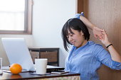 A young Japanese businesswoman is taking a break from work and stretching her arms in front of a laptop at her home-office. A young Japanese student is taking a break from homework and stretching her