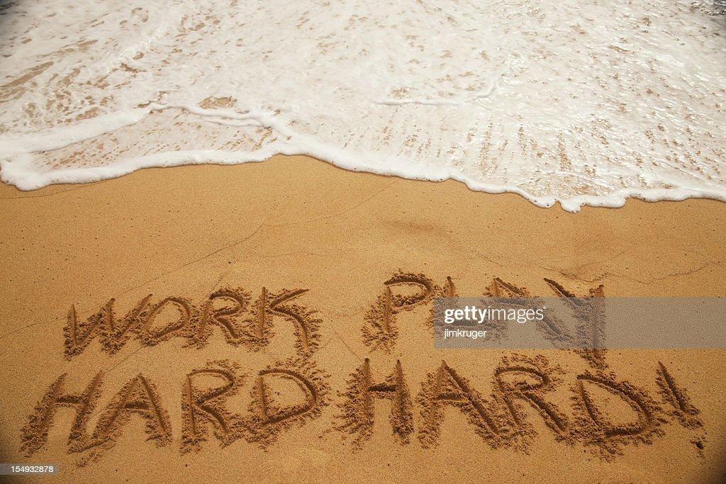 'Work Hard Play Harder' written in beach sand.