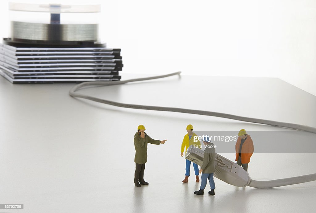 work men miniatures holding computer cable : Stock Photo