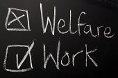 The words Welfare and Work written on a blackboard with a tick in the box to express a desire or preference for work.