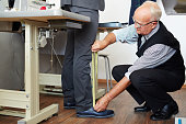 Fashion designer measuring length of trousers