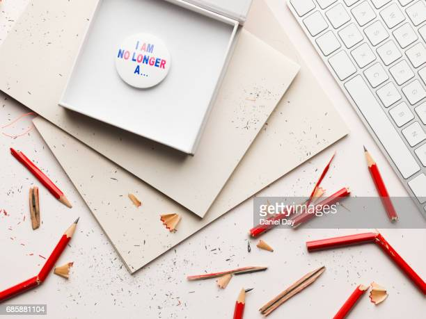 Work or home desk with a pile of notebooks and an open box containing a badge on top, broken pencils all around