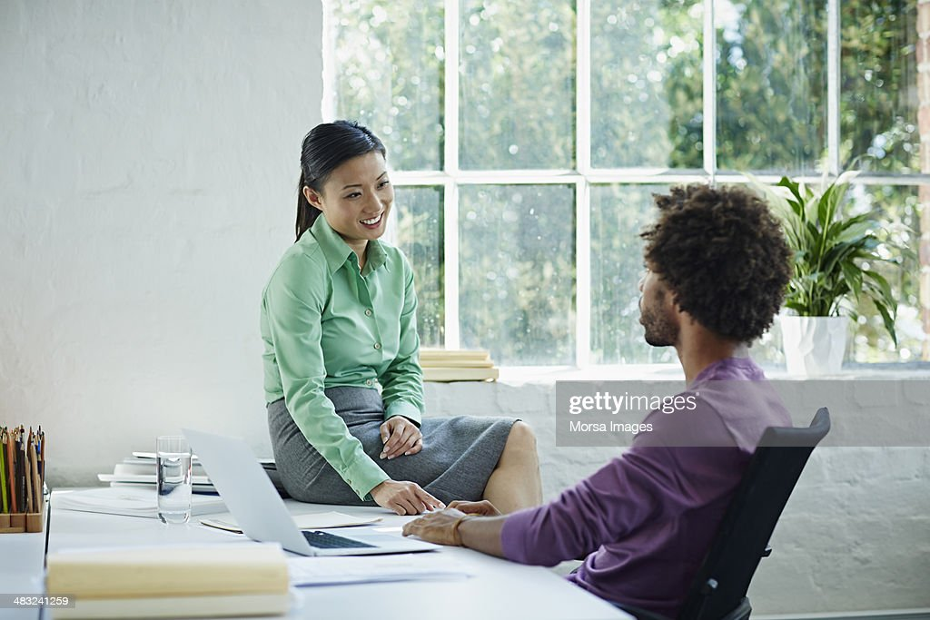 Work peers engaged in a conversation : Stock Photo