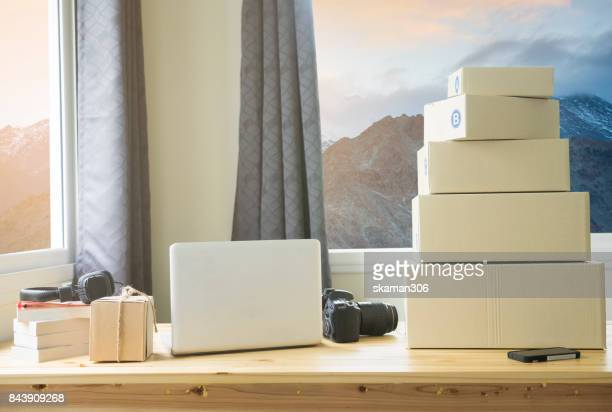 work space of online Seller with laptop computer and camera and package ready to shipped with Mountain and landscape