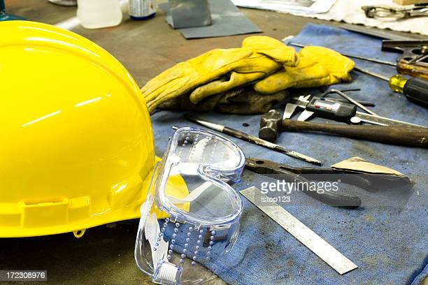 Workbench with safety goggles, pliers, hammer, gloves and hardhat.
