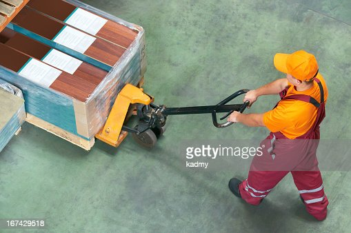 Worked with a fork pallet truck picking things up : Stock Photo