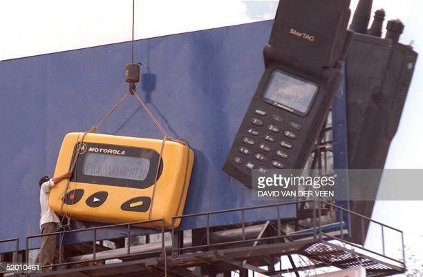 A worker 23 June struggles to install an oversized copy of a pager on a central Phnom Penh billboard advertising Motorola products As landlinebased...