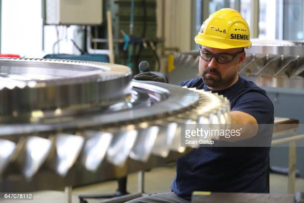 A worker adds blades to a disc of a turbine at the Siemens gas turbine factory on March 2 2017 in Berlin Germany Germany's number of unemployed fell...