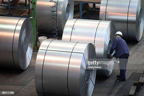 A worker adds inner support rings to coils of galvanized steel at the ArcelorMittal Eko Stahl steelworks on January 26 2010 in Eisenhuttenstadt...