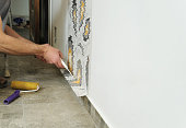 Worker adhesive wallpapers. He presses for better wallpaper adhesive using a roller and scraper.