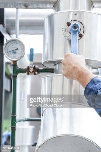 Worker adjusting control lever on industrial equipment