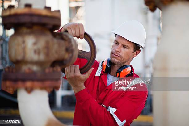 Worker adjusting gauge at chemical plant