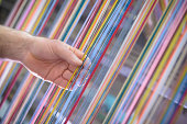 Worker adjusting multicoloured silk yarn on industrial loom in textile mill
