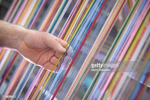 Worker adjusting multicoloured silk yarn on industrial loom in textile mill