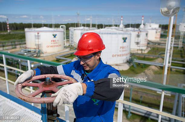 A worker adjusts a valve wheel on pipework at an oil plant operated by Salym Petroleum in Salym KhantyMansi autonomous region Russia on Wednesday...