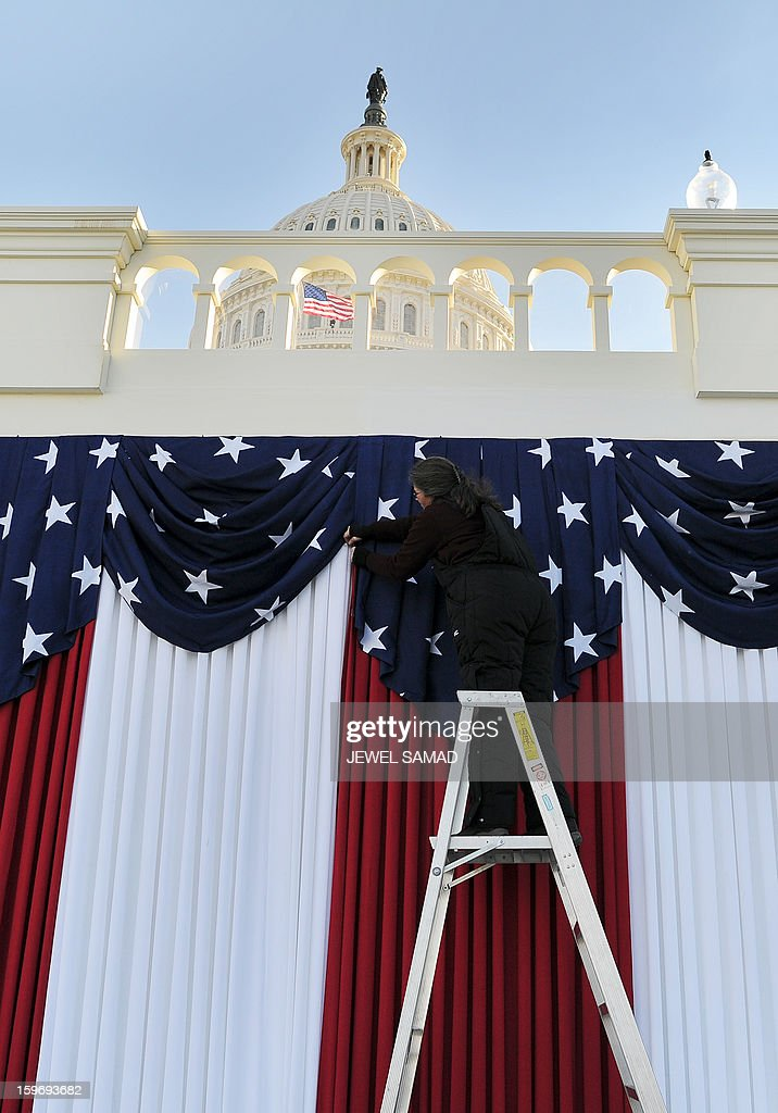 A worker adjusts flags on the US Capitol as preparations continue for the second inauguration of US President Barack Obama in Washington on January 18, 2013. Crowds may be smaller at the January 21 inauguration than when Barack Obama was first sworn into office in 2009, but security is as tight as ever, with experts warning a 'lone wolf' would pose the greatest threat. Between 500,000 and 800,000 people are expected to pass through the National Mall, the immense greenway that leads up to the Capitol, compared to the 1.8 million spectators who came to applaud Obama four years ago. AFP PHOTO/Jewel Samad