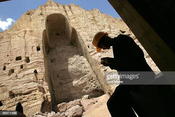 A worker adjusts his radio in front of an alcove which used to contain a giant Buddah overlooking the area September 5 2005 in Bamiyan Afghanistan...