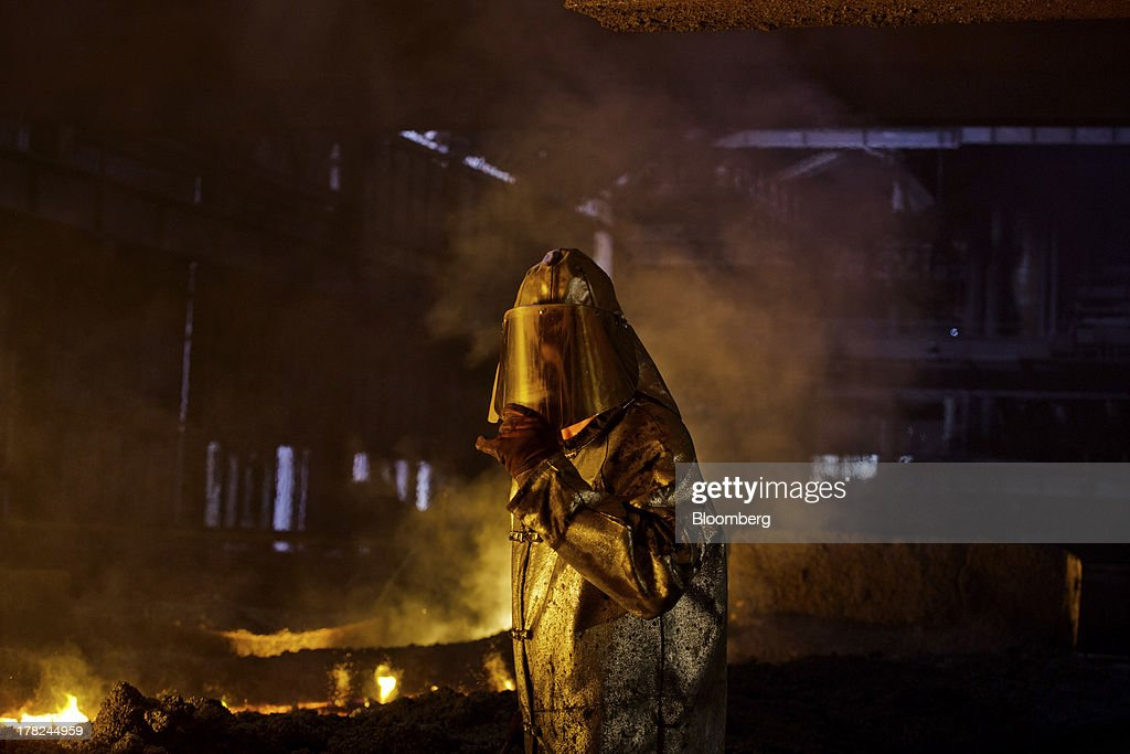 A worker adjusts his safety visor as he operates in the blast furnace in at ArcelorMittal's steel plant in Ostrava, Czech Republic, on Monday, Aug. 26, 2013. ArcelorMittal, the world's biggest steelmaker, said steel shipments will rise 1 percent to 2 percent this year compared with an earlier forecast of 2 percent in May. Photographer: Martin Divisek/Bloomberg via Getty Images