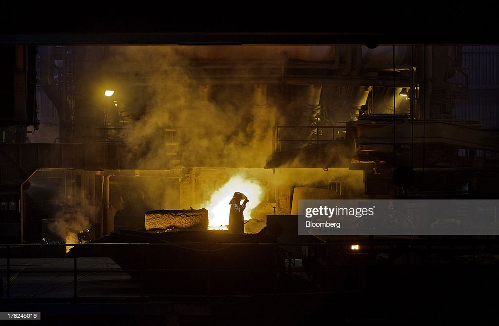 A worker adjusts his safety visor as he works near the blast furnace at ArcelorMittal's steel plant in Ostrava, Czech Republic, on Monday, Aug. 26, 2013. ArcelorMittal, the world's biggest steelmaker, said steel shipments will rise 1 percent to 2 percent this year compared with an earlier forecast of 2 percent in May. Photographer: Martin Divisek/Bloomberg via Getty Images
