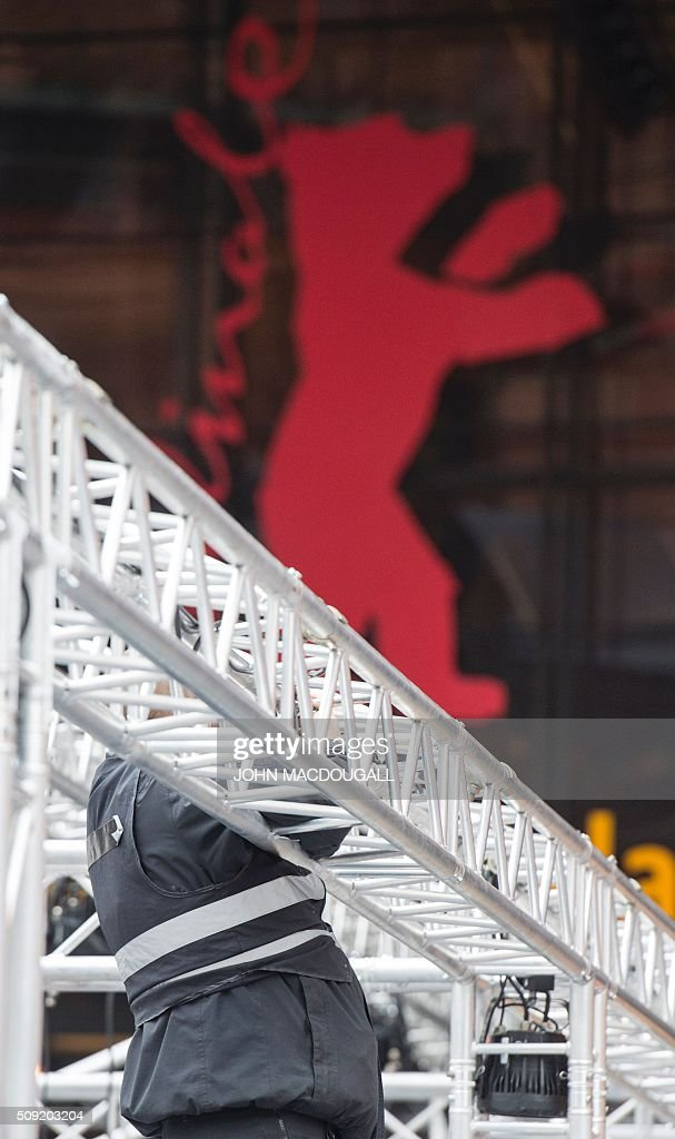 A worker adjusts railing in front of the Berlinale Film Festival's main venue, the Berlinale Palast in Berlin on February 9, 2016. The 66th Berlin film festival starts February 11 with a spotlight on Europe's refugee crisis. / AFP / John MACDOUGALL