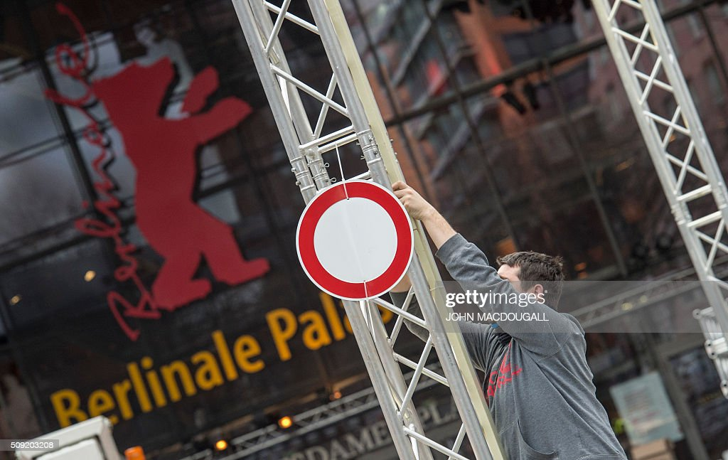 A worker adjusts railing in front of the Berlinale Film Festival's main venue, the Berlinale Palast, in Berlin on February 9, 2016. The 66th Berlin film festival starts February 11 with a spotlight on Europe's refugee crisis. / AFP / John MACDOUGALL