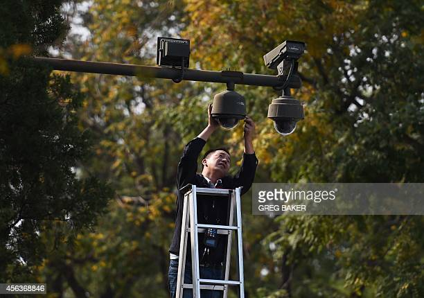 A worker adjusts security cameras on the edge of Tiananmen Square in Beijing on September 30 2014 The country will mark National Day the 65th...
