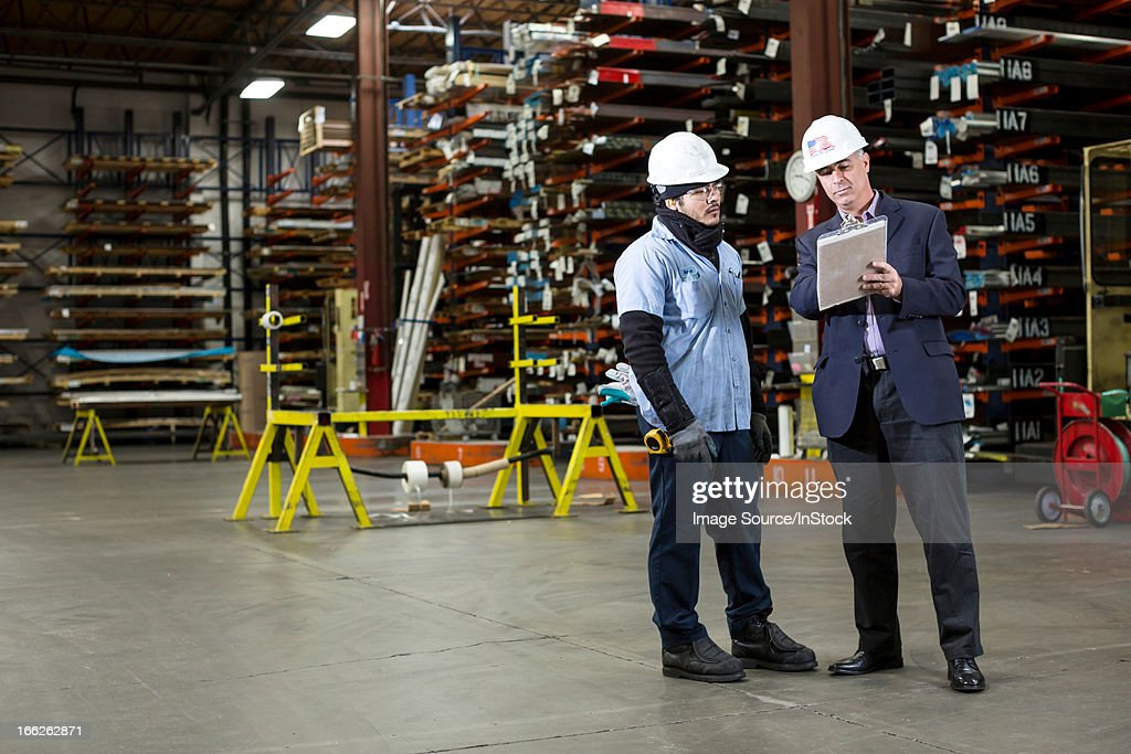 Worker and businessman in metal plant : Stock Photo