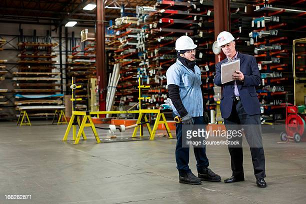 Worker and businessman in metal plant