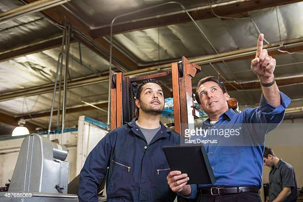 Worker and businessman talking in warehouse