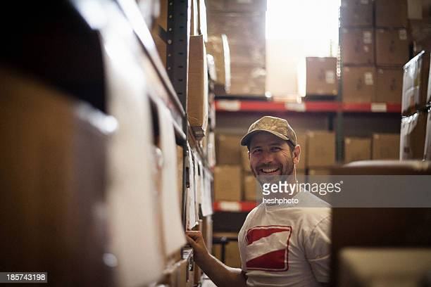Worker and cardboard boxes stored in warehouse