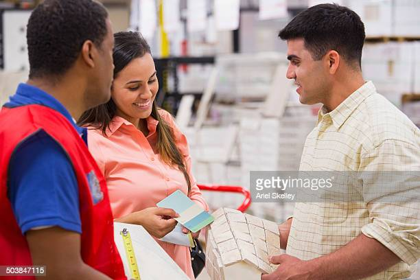 Worker and couple discussing plans in home improvement store
