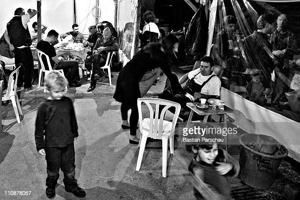 A worker and guests during a raki production waiting the first raki at the distillery on October 23 2009 in Heraklion Greece Raki is a distillate of...