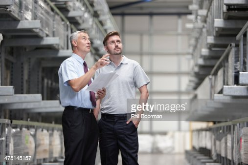 Worker and manager checking products in engineering warehouse