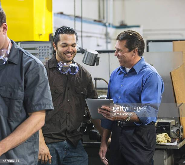 Worker and manager using digital tablet in warehouse
