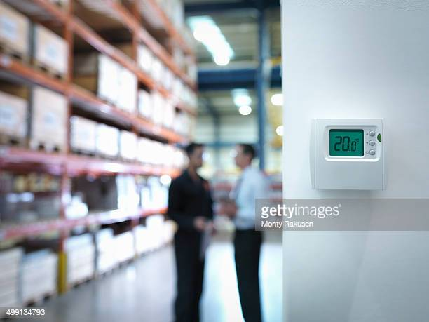 Worker and office manager discuss energy use near thermostat in factory