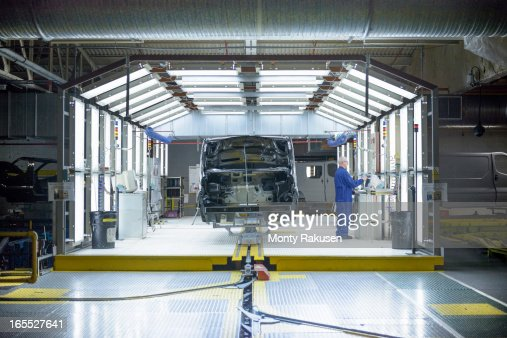 Worker and vehicle in inspection station in car factory
