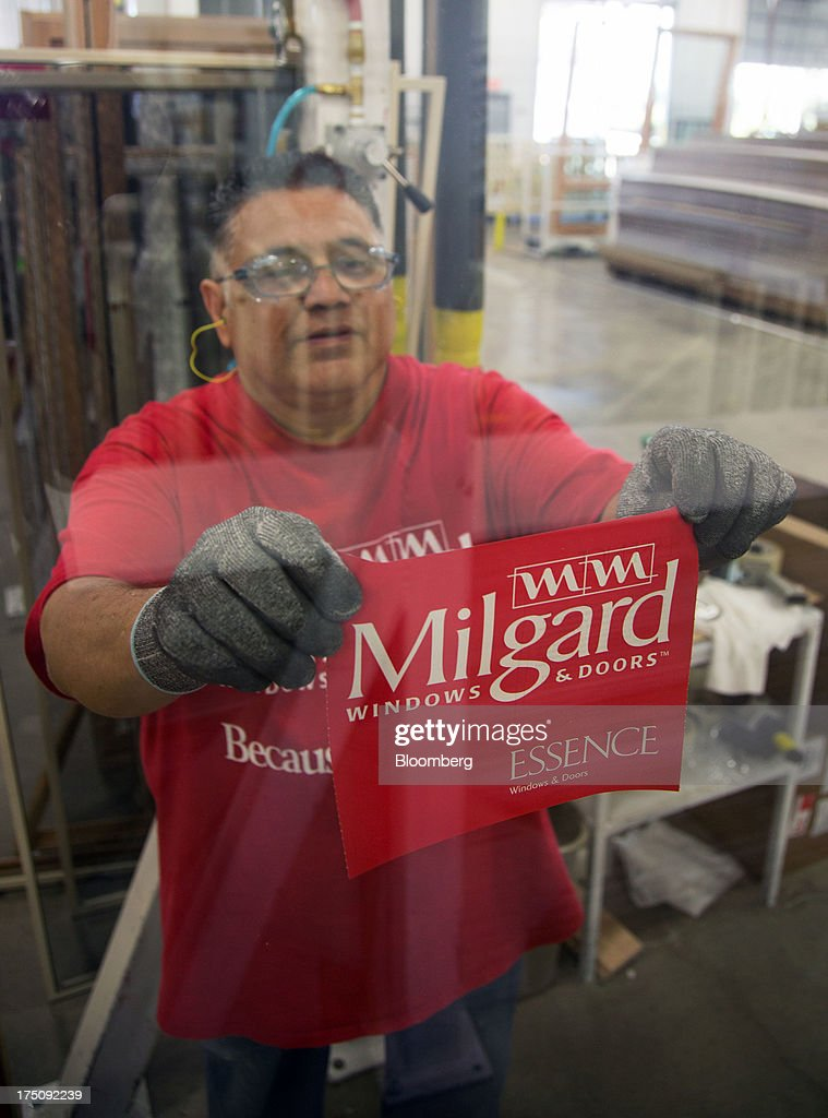 A worker applies an Essence series sticker on a finished window at the Milgard Windows & Doors' manufacturing facility in Tacoma, Washington, U.S., on Wednesday, July 24, 2013. The U.S. Census Bureau is scheduled to release monthly factory orders figures on Aug. 2. Photographer: Tim Rue/Bloomberg via Getty Images