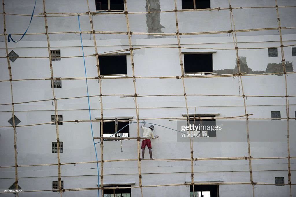 A worker applies paint to a building while standing on bamboo scaffolding at a construction site at Yangon on May 3, 2016. The resource-rich country now has one of the fastest growing economies in the world, and commercial hub Yangon has morphed from a crumbling relic to a rapidly transforming metropolis, with an ever-changing skyline. / AFP / YE