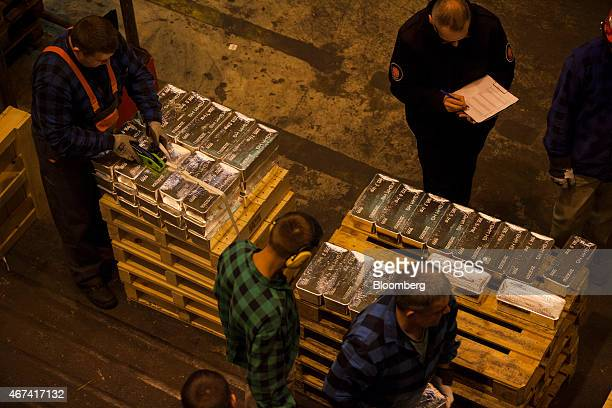 Worker arrange palettes of newly cast silver bullion bars for export at the KHGM Polska Miedz SA smelting plant in Glogow Poland on Monday March 23...