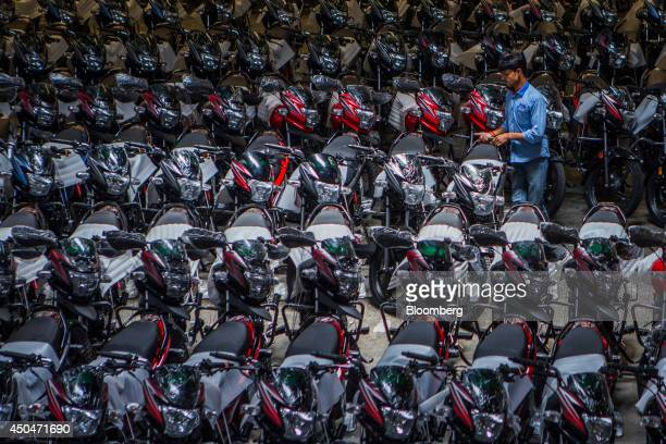 A worker arranges a motorcycle for shipping in the dispatch bay of the Hero MotorCorp Ltd manufacturing facility in Gurgaon India on Wednesday June...