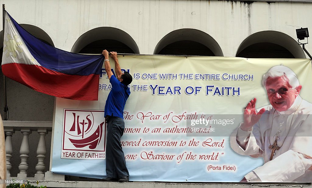 A worker arranges a Philippine flag next to a portrait of Pope Benedict XVI displayed outside an office building in Manila on February 12, 2013. People across the mainly Catholic Philippines feel regret, gratitude and sympathy after Pope Benedict XVI announced plans on February 11 to resign, a presidential spokesman said. The Catholic Church entered uncharted waters on February 12 after Pope Benedict XVI's shock announcement that he would become the first pontiff to resign of his own free will in 700 years.
