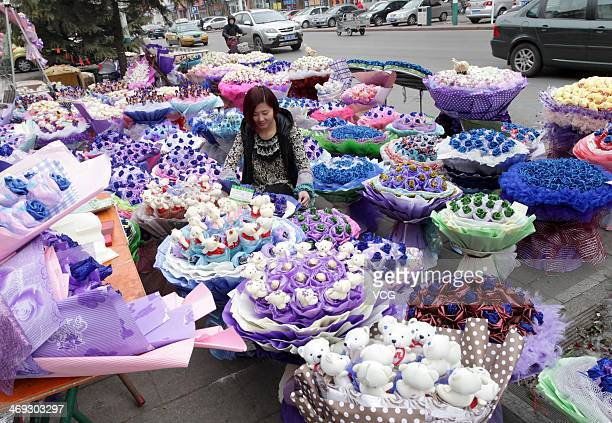 A worker arranges bouquets of roses at a flower shop on February 13 2014 in Weifang China
