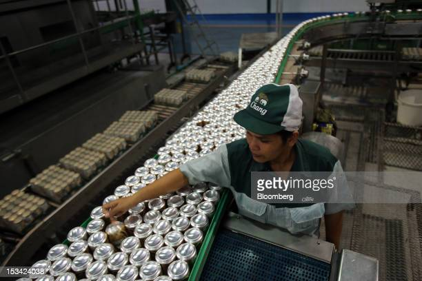 A worker arranges cans of Thai Beverage Pcl Chang beer on a conveyor system as they move along the production line at the company's Beer Thip brewery...
