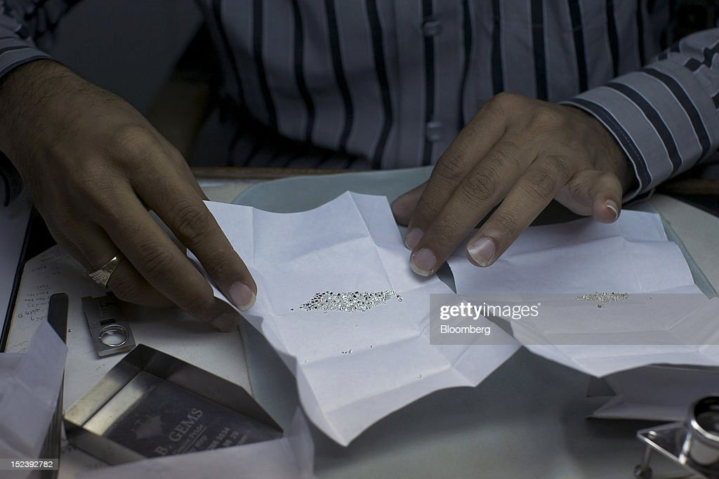 A worker arranges diamonds for a photograph inside a diamond cutting and polishing workshop in Mumbai, India, on Monday, Sept. 17, 2012. Sales of diamond jewelry in India are set to rise 16 percent annually in the five years to 2015, twice as fast as the 7 percent growth predicted for adornments made of the yellow metal, according to a study by New Delhi-based consultants AM Mindpower Solutions. Photographer: Adeel Halim/Bloomberg via Getty Images