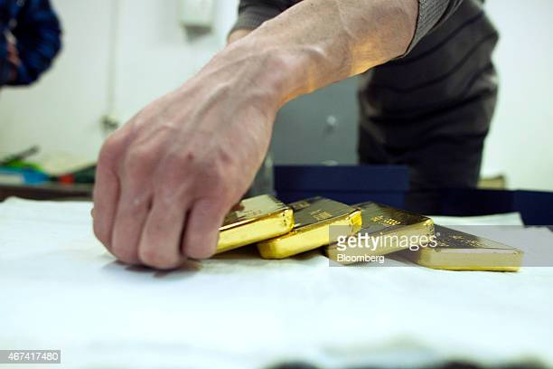 A worker arranges newly cast gold bullion bars in a saferoom ahead of export at the KHGM Polska Miedz SA smelting plant in Glogow Poland on Monday...