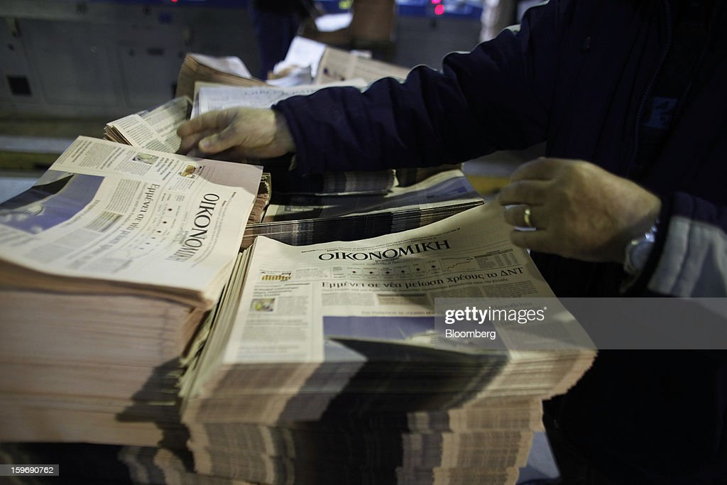 A worker arranges newly-printed financial sections of the Kathimerini newspaper at the Kathimerini printing plant in Paiania, Greece, on Thursday, Jan. 17, 2013. An anarchist group claimed responsibility for a series of attacks early on Jan. 11 when unidentified perpetrators threw makeshift bombs made from propane gas canisters into the homes of five Greek journalists working for national media saying it was to protest coverage of the country's financial crisis seen as sympathetic to the government. Photographer: Kostas Tsironis/Bloomberg via Getty Images