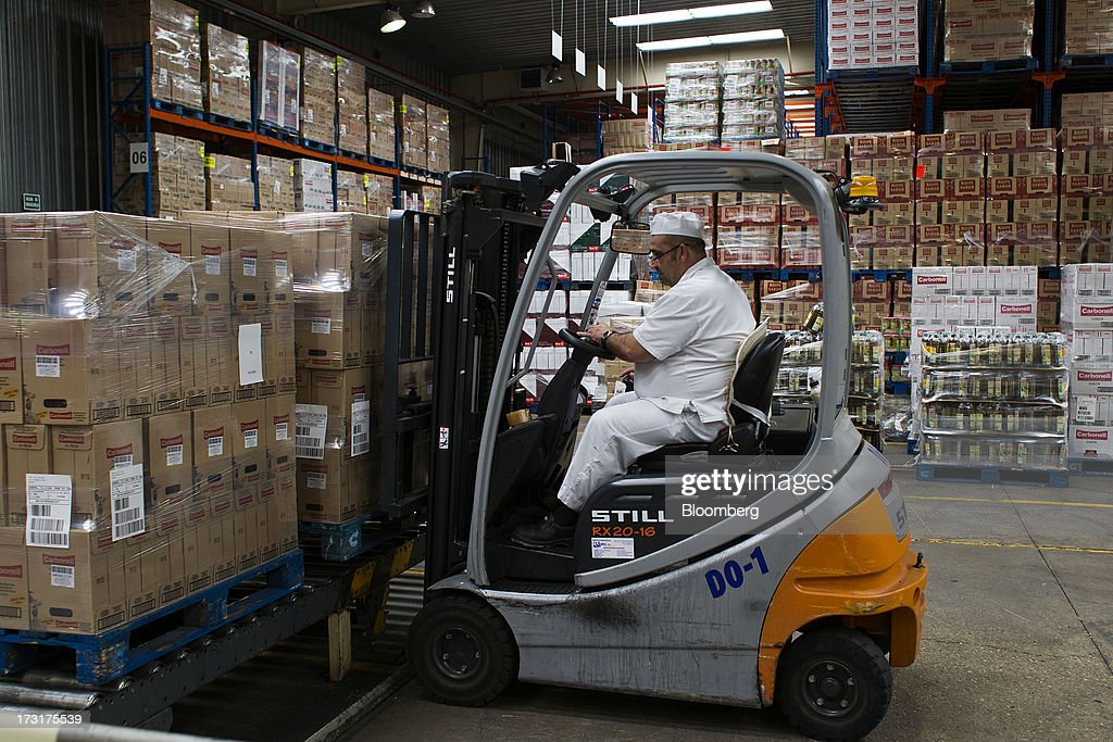 A worker arranges pallets of packaged Spanish olive oil using a fork lift truck in a warehouse at the Carbonell SA plant, operated by Deoleo SA, in Alcolea, Spain, on Tuesday, July 9, 2013. JPMorgan was asked to explore sale of more than 30% stake in olive oil company Deoleo, Reuters reports, citing two people close to the deal. Photographer: Angel Navarrete/Bloomberg via Getty Images
