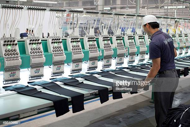 A worker arranges pieces of fabric under embroidery machines inside the Esquel Group garment factory at the VietnamSingapore Industrial Park in Thuan...